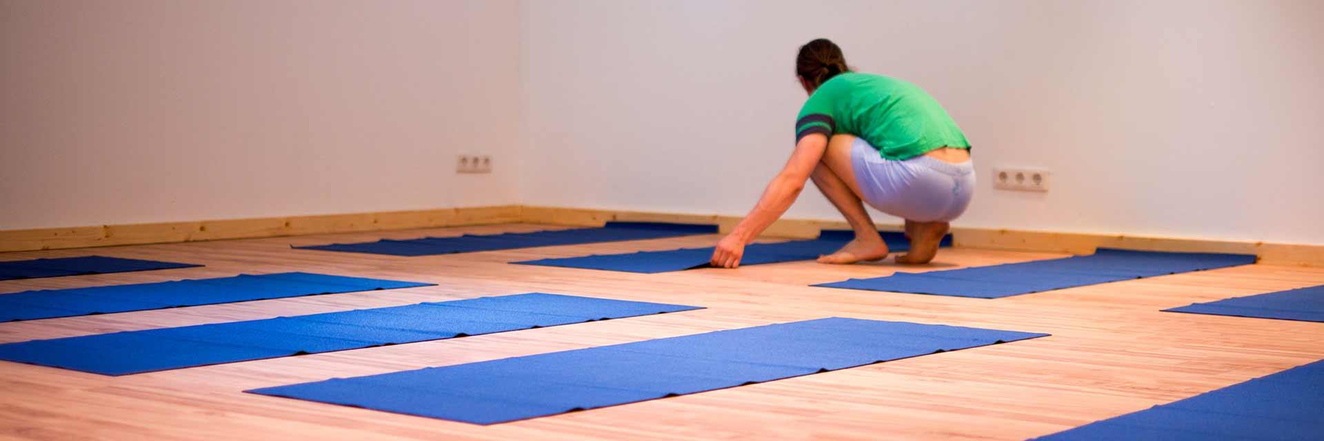 Sie sehen Yoga-Lehrer Florian Pfeifer bei vorbereiten der Yoga-Matten im Adamus Yoga Studio in Bad Säckingen.