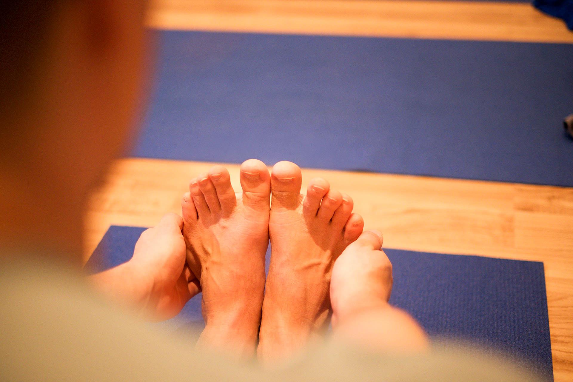 Hande bei den Füßen in Paschimottanasana sitzende Vorbeuge